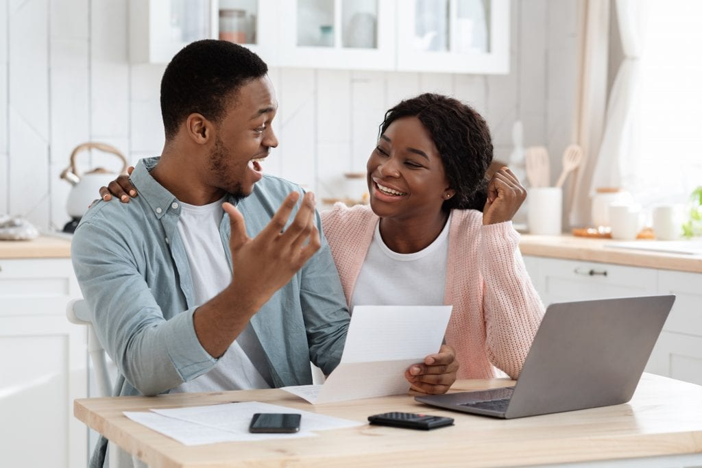 Portrait Of Happy Excited Black Married Couple Reading Insurance Documents In Kitchen, Joyful African American Family Celebrating Success, Got Taxes Refund Or Work Promotion Letter, Closeup
